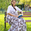 Happy pregnant womreading book in nice garden — Stock Photo #12274631