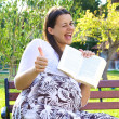 Pregnant woman with book thumb up — Stock Photo