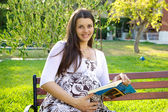 Beautiful pregnant woman reading book — Stock Photo
