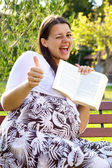 Happy pregnant woman with book thumb up — Stock Photo