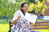 Pregnant woman with book thumb up — Стоковое фото