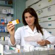 Beautiful pharmacist woman showing medicine — Stock Photo #12400812