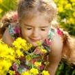 Little blonde girl inhales scent of flowers — Stock Photo #10897188