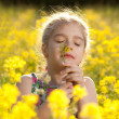 Little girl enjoys the smell of flowers — Stockfoto