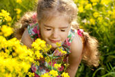 Little blonde girl inhales scent of flowers — Stock Photo