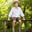 Stock Photo: Boy in hat and shorts sitting on bench