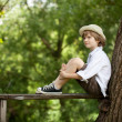 Stock Photo: Boy sits on wooden bench