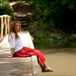 Royalty-Free Stock Photo: Young woman sitting on the bridge