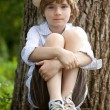Boy in the hat on the bench - Stock Photo