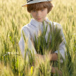 Stock Photo: Boy is among ears of wheat