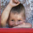Kid is situated near the window — Stock Photo