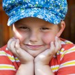 Boy in blue cap sits — Stock Photo #12166496