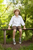 Boy in the hat and shorts sitting on a bench — Stock Photo