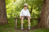 Fair-haired boy in a hat, shirt, shorts — Stock Photo