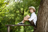 Boy sits on a wooden bench — Stock Photo