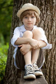 Boy in the hat on the bench — Stock Photo