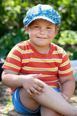 Cheerful boy sitting on a stump — Stock Photo