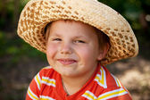 Smiling boy in a wicker hat — Stock Photo