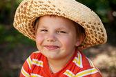 Smiling boy in a wicker hat — Stock Photo