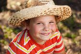 Gelukkige jongen in een stro hoed — Stockfoto