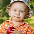 Charming babe in panama eating delicious apple — Stock Photo