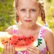 Cute girl with pigtails eating a watermelon — Stock Photo