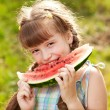 Funny, dark-haired girl with pigtails eating a watermelon — Stock Photo