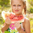 Blonde girl with pigtails eating a watermelon — Stock Photo