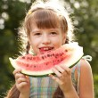 Royalty-Free Stock Photo: Funny little girl with pigtails eating a watermelon