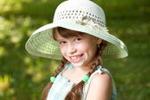 Happy girl with braids in the hat — Stock Photo