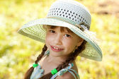 Dark-haired girl in a hat and dress — Stock Photo