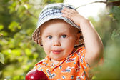 Kid in panama with red apple — Stock Photo
