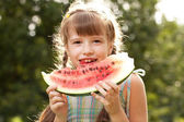Funny little girl with pigtails eating a watermelon — Stock Photo