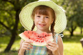 Girl in hat eating a watermelon — Stock Photo