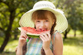 Girl in hat eating a red watermelon — Stock Photo