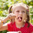 Girl with pigtails eats with relish ice cream — Stock Photo
