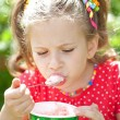Girl in a red blouse with relish eating ice cream — Stock Photo