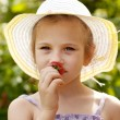 Girl in the hat smells fresh strawberries — Stock Photo