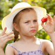 Girl in a summer hat considers strawberries — Stock Photo