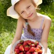 Smiling girl with a big bowl of strawberries — Stock Photo