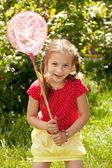 Girl tries to catch butterflies — Stock Photo