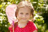 Menina sorridente com uma rede de borboletas — Foto Stock