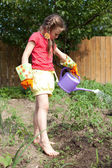 Girl watering a flower bed garden — Stock Photo