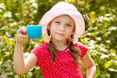 Girl in the summer panama with a cup — Stock Photo