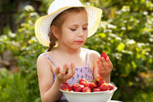 Girl in a summer hat and dress eating strawberries — Stock Photo
