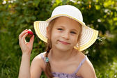 Little girl is enjoying a delicious strawberries — Stock Photo