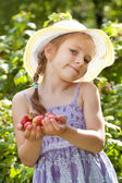 Cheerful girl holding a ripe strawberries — Stock Photo