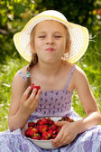 Little girl enjoys a ripe strawberry — Stock Photo