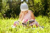 Encantadora menina de chapéu lendo um livro — Foto Stock