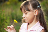 Cute little girl playing with a flower — Stock Photo